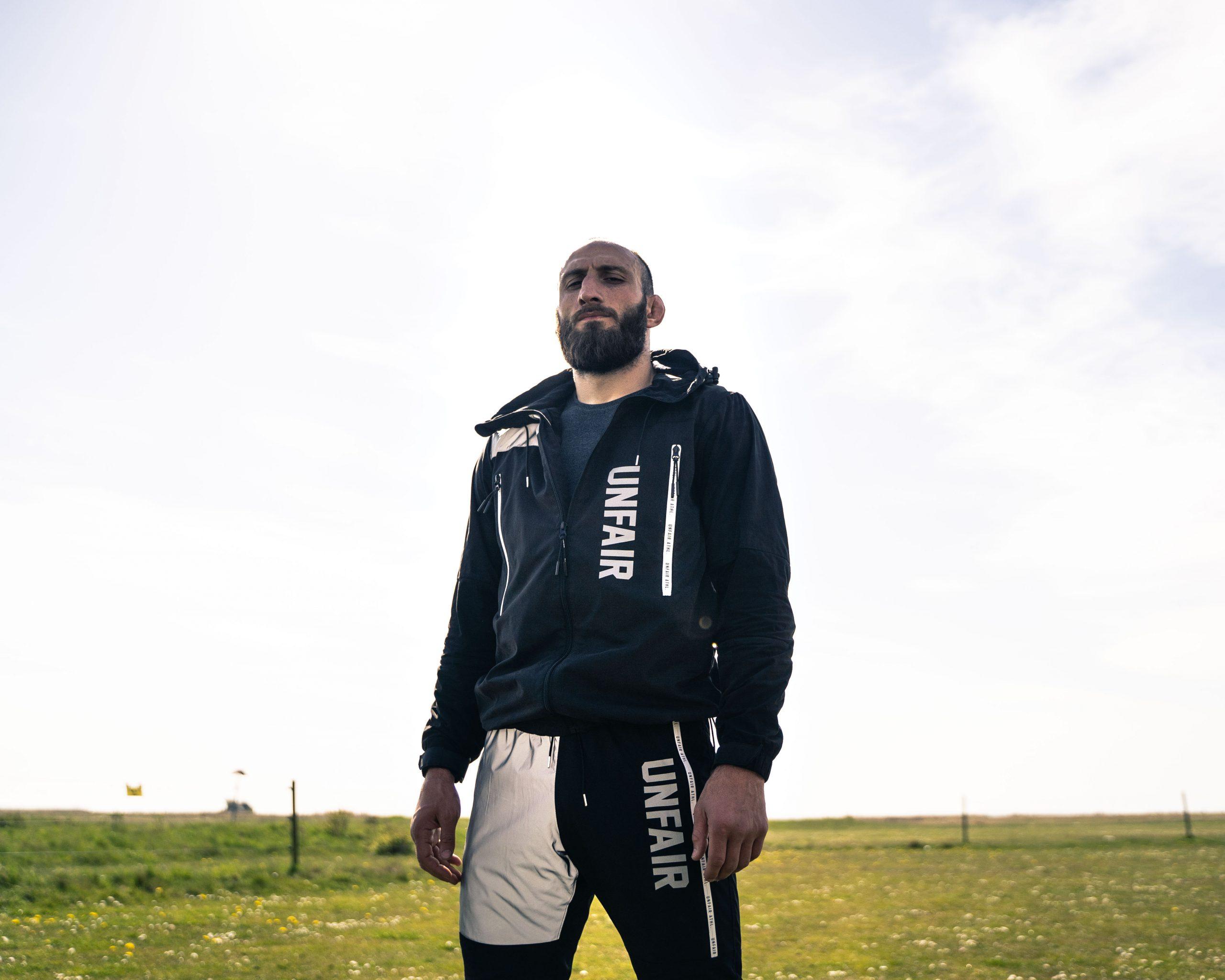 Guram The Georgian Viking Kutateladze, person som står i ett gräsplan utomhus med ljus himmel. Bär på sig mörka träningskläder.