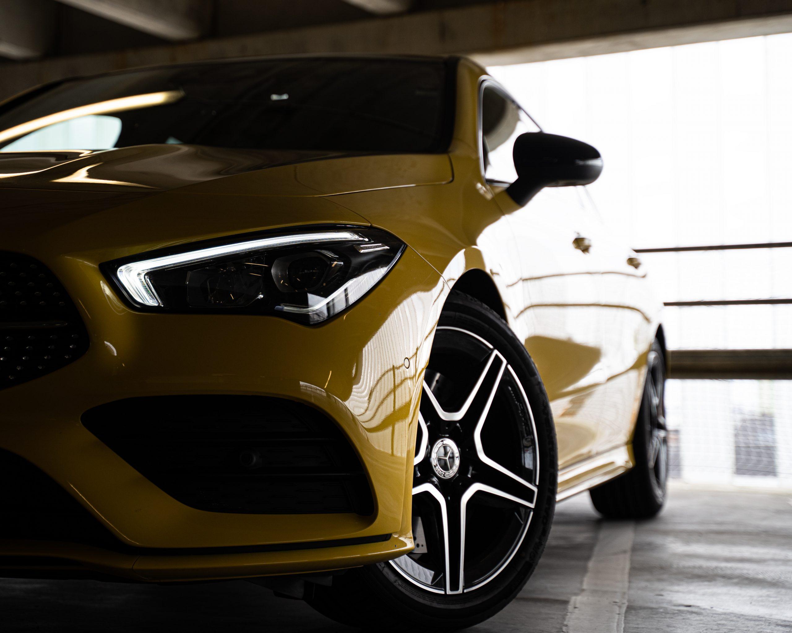 Halv vänster framsida av gul Mercedes Benz CLA220 2020 i ett mörkt parkeringshus med ljus från vänster av bilen.