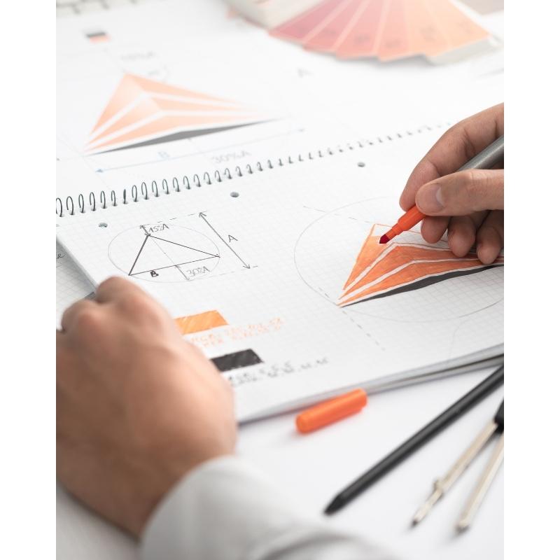 Reklambyrå i Malmö, person som formger och färglägger en logga på rutad papper