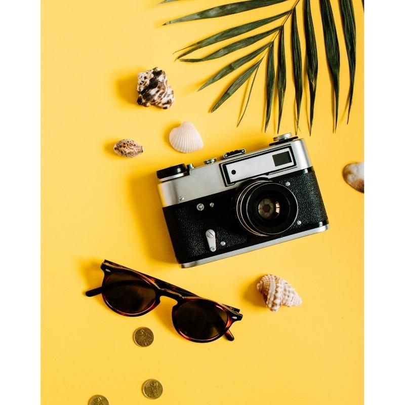 Olika föremål som består av ett par solglasögon, tre mynt, fem snäckor, e kompakt systemkamera, blad från en växt på en gul bakgrund