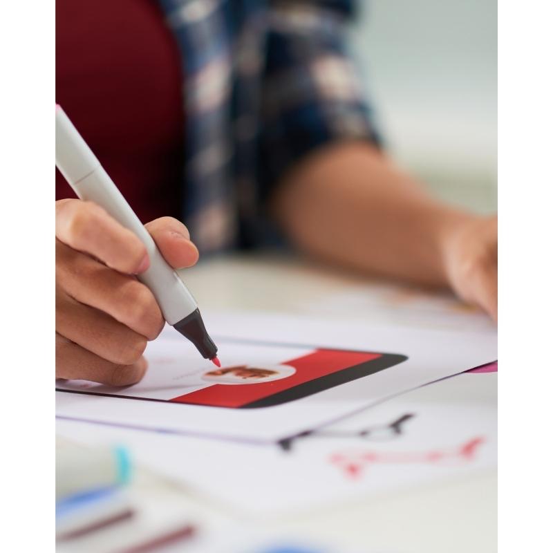Individ som formger och färglägger ett gränssnitt på papper som skapar ett visuell identitet för varumärket